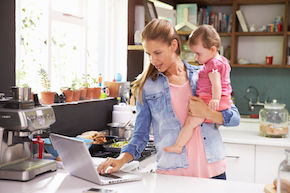 mother with young daughter using laptop in kitchen